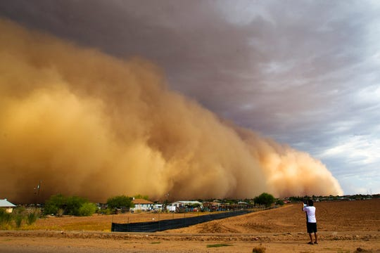 A dust storm engulfs a neighborhood on the Salt River Reservation. Winds caused outages that left about 10,000 customers of Salt River Project and Arizona Public Service Co. without electricity at the storm's peak. In Pinal County, officials reported cars pulled off the road due to zero visibility.