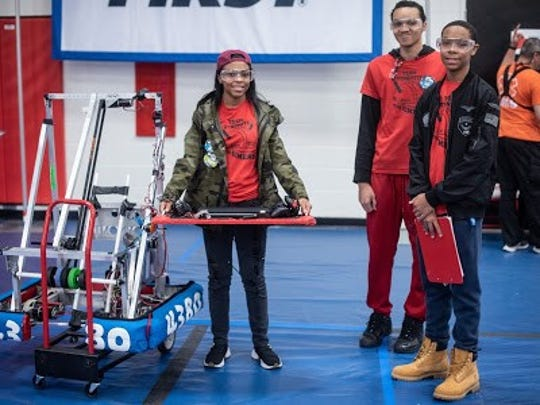 From left, members of Heroes' Alliance Team 4380 Dynomite Olivia McKinstry, Emmanue'l Franklin and Andrew McKinstry pause for a photo as they prepare to enter the robotics field to compete.