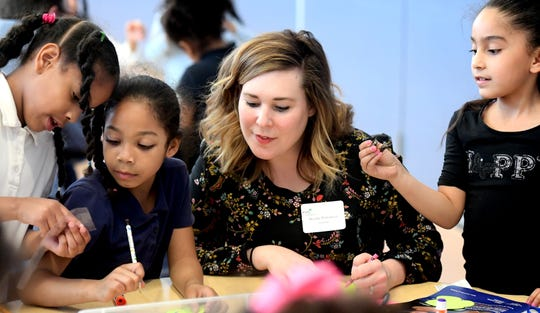Brandy Portonova of Glatfelter Insurance Group, looks in on the work of girls scouts, and Ferguson K-8 first graders, from left, Diasmerlin Contreras, Aniyah Owens and Edwrishka Vega Correa, during a STEAM after-school program at the school Wednesday, April 24, 2019. Girl Scouts in the Heart of Pennsylvania partnered with Martin Library to offer York City students access to its mobile programming through the district's after-school programs. Corporate sponsors, like Glatfelter, visited the program during its session Wednesday. Bill Kalina photo