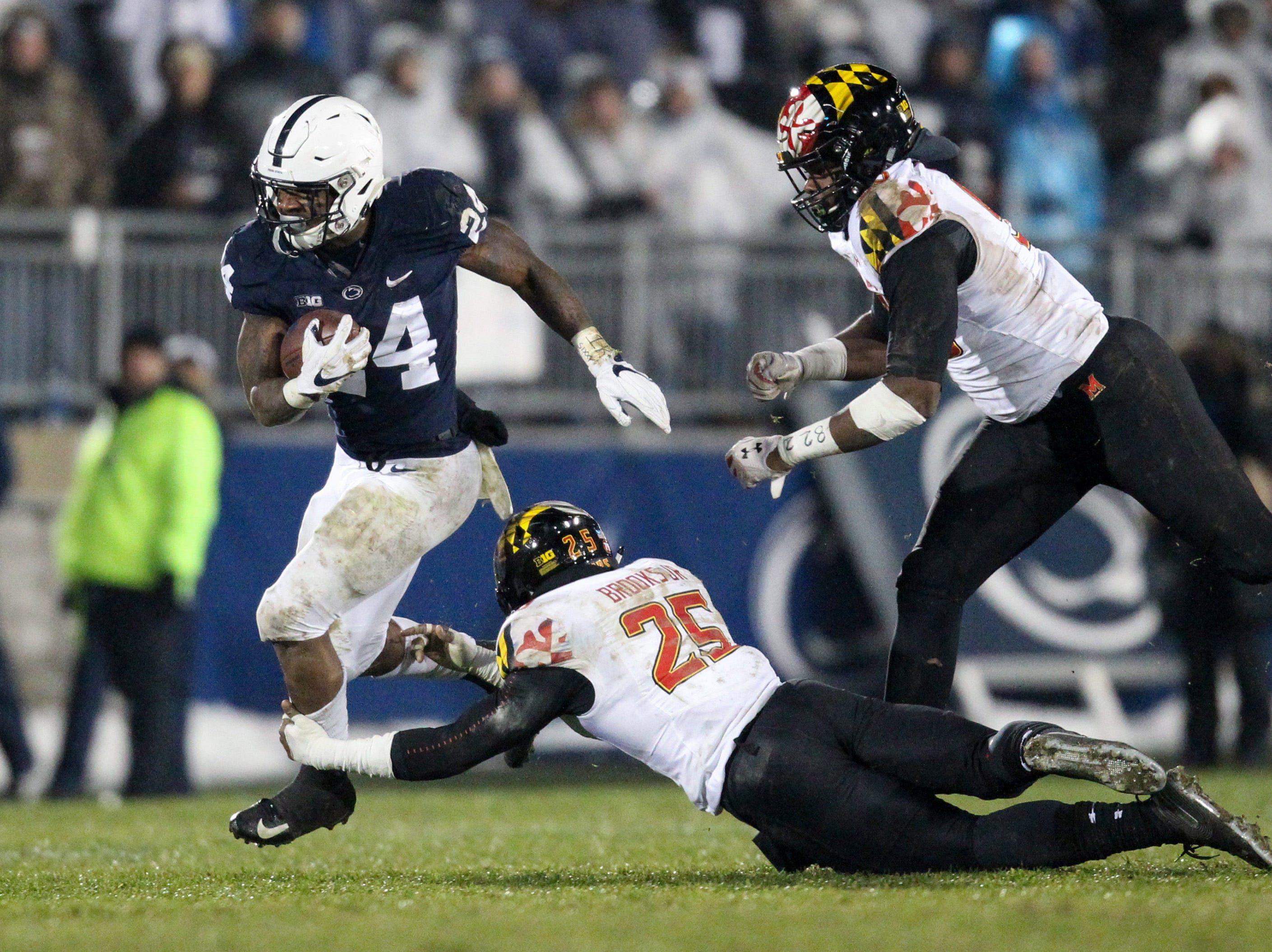 Nov 24, 2018; University Park, PA, USA; Penn State Nittany Lions running back Miles Sanders (24) runs with the ball while avoiding a tackle from Maryland Terrapins defensive back Antoine Brooks Jr (25) during the third quarter at Beaver Stadium. Penn State defeated Maryland 38-3. Mandatory Credit: Matthew O'Haren-USA TODAY Sports