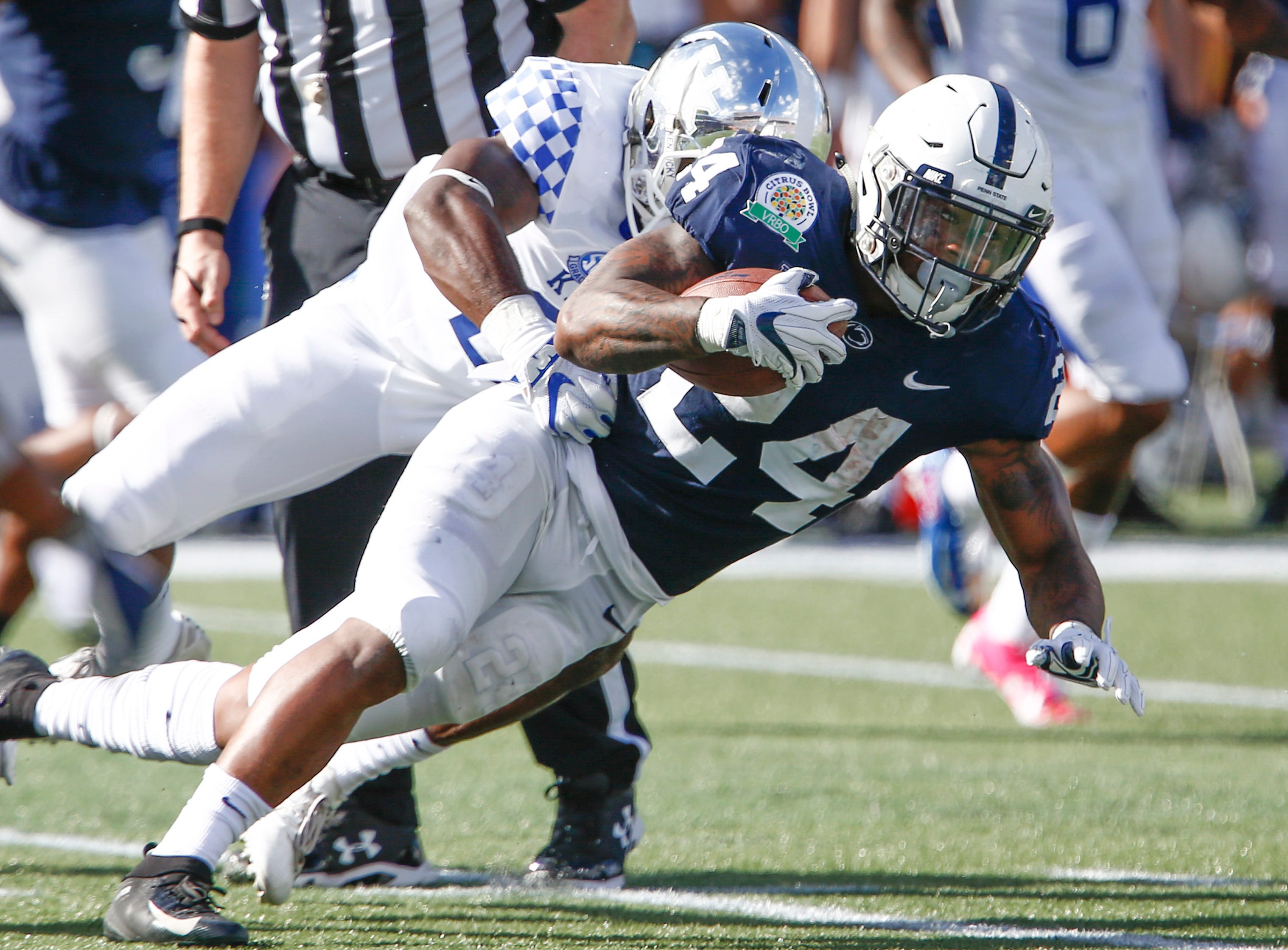 Jan 1, 2019; Orlando, FL, USA; Kentucky Wildcats linebacker Chris Oats (22) tackles Penn State Nittany Lions running back Miles Sanders (24) during the second quarter in the 2019 Citrus Bowl at Camping World Stadium. Mandatory Credit: Reinhold Matay-USA TODAY Sports