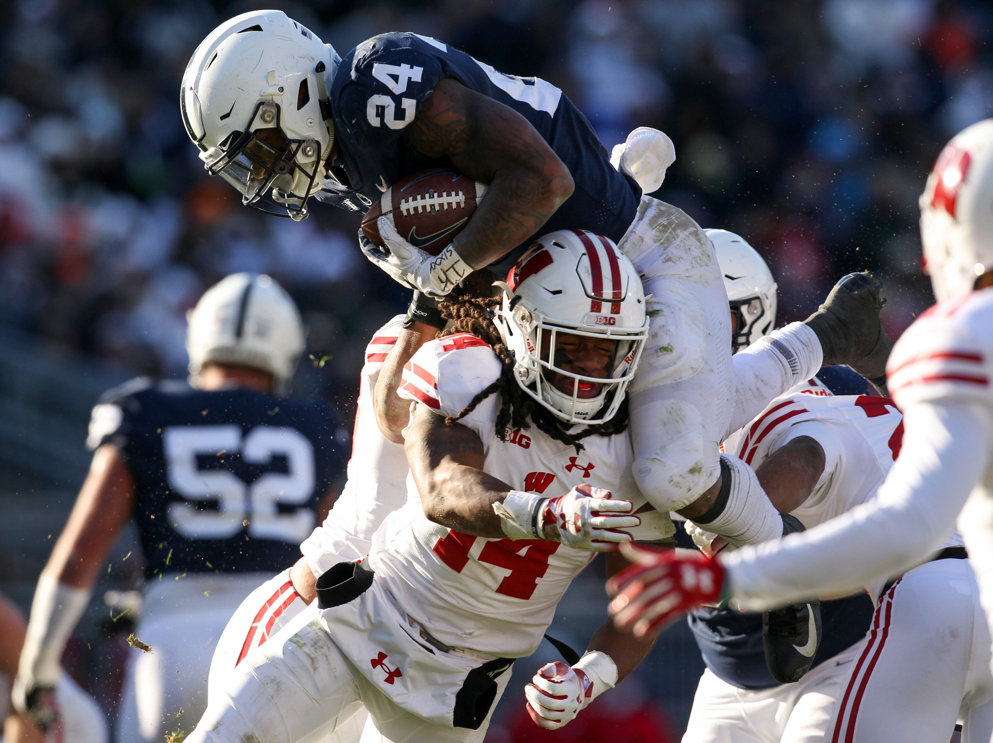 Nov 10, 2018; University Park, PA, USA; Penn State Nittany Lions running back Miles Sanders (24) leaps over Wisconsin Badgers safety D'Cota Dixon (14) during the fourth quarter at Beaver Stadium. Penn State defeated Wisconsin 22-10. Mandatory Credit: Matthew O'Haren-USA TODAY Sports