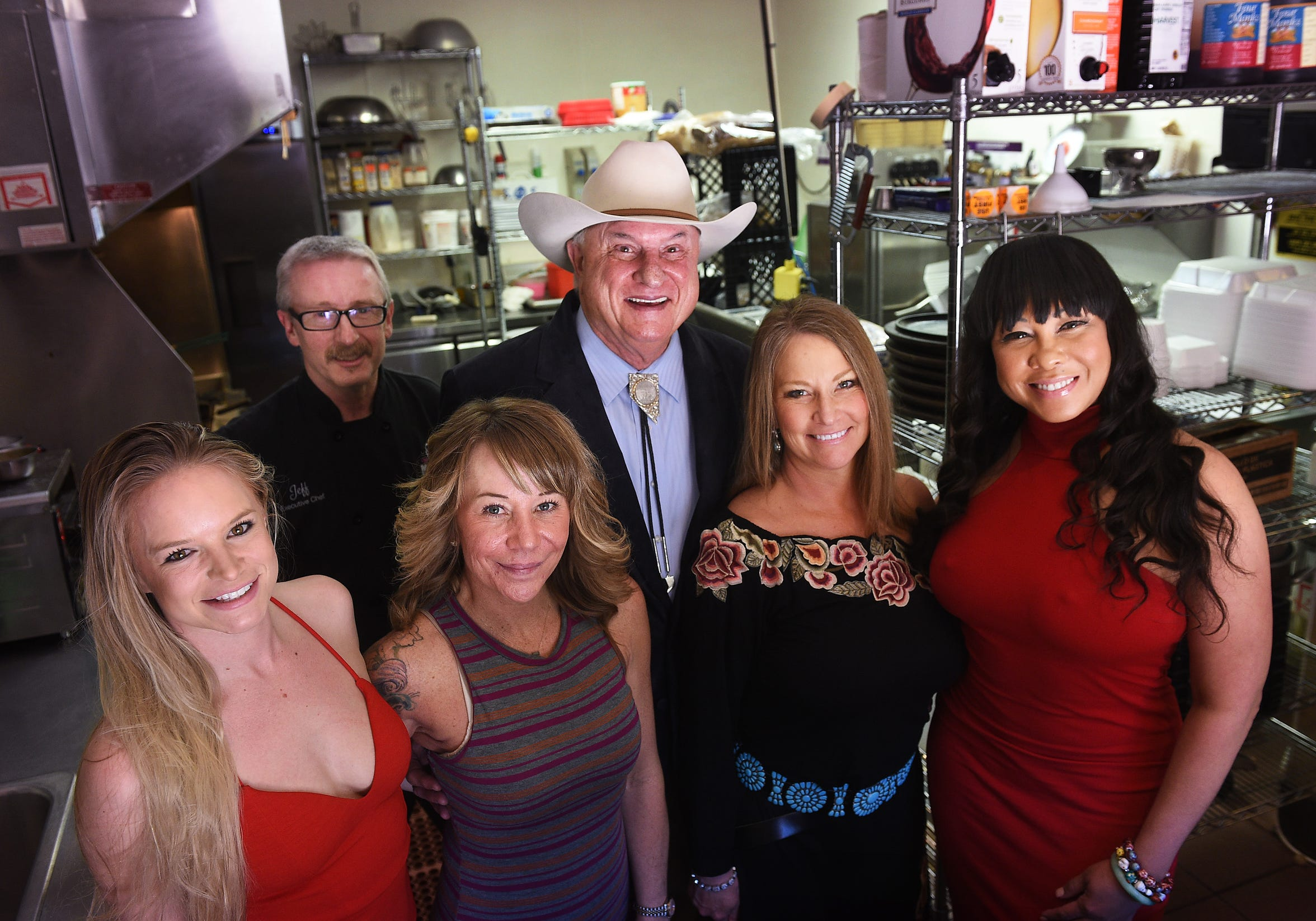 Mustang Ranch owner Lance Gilman, back middle, poses for a portrait with, from left, working lady Jasper Dayton, Chef Jeff Probus, madam Tara Adkins, madam Jennifer Barnes and working lady Ayana in the kitchen of the brothel resort about 15 miles east of Reno.