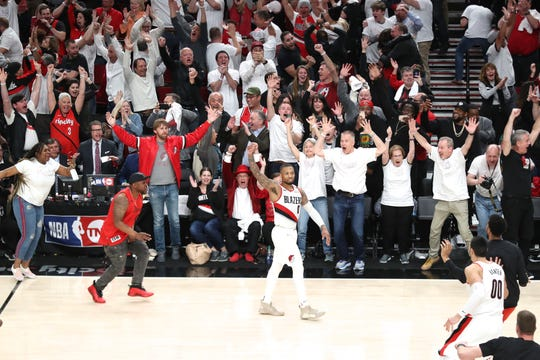 Trail Blazers guard Damian Lillard reacts after making a three-point shot over Oklahoma City Thunder forward Paul George.