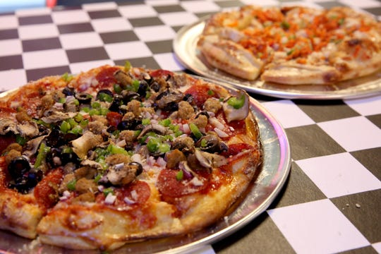 The Station Wagon, front, a pizza with pepperoni, Italian sausage, black olives, mushrooms, green peppers and red onion with mozzarella and a marinara sauce and the Tuk Tuk, a pizza with grilled chicken, shredded carrot, red peppers and green onion with mozzarella on a Thai peanut sauce at the Turn Here Bar and Grill in Turner on April 24, 2019. The former garage, converted into a pizza parlor opened April 10.