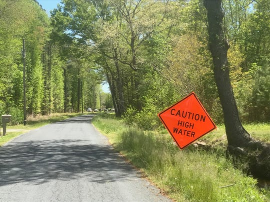 This sign warns of high water farther down Bells Neck Road in Accomack County, Virginia. Residents are concerned about frequent flooding of the road.