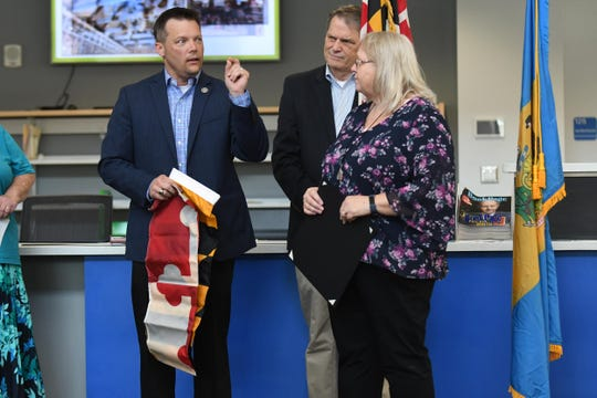 Maryland State Representative Carl Anderton presents Library Director Susan Upole with a Maryland Flag that was flown over the State House in Annapolis during the Dedication of the Delmar Public Library on Wednesday, April 24, 2019.