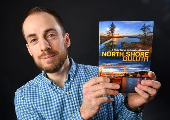 Photographer David Barthel holds a copy of his book Wednesday, April 24, in St. Cloud.
