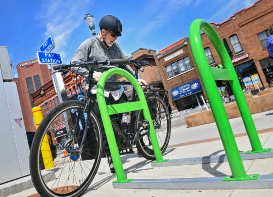 Kurt Franke positions his bicycle on one of the newly-installed green bike racks at the intersection of Fifth Avenue South and First Street South Wednesday, April 24, in St. Cloud.