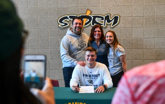 J.D. Bates poses for a photograph with his family during the Sauk Rapids Senior Signing Day ceremony Wednesday, April 24, at Sauk Rapids-Rice High School.