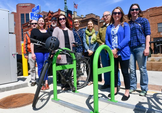 Members of Bike St. Cloud gather around one of the newly installed green bike racks at Fifth Avenue South and First Street Wednesday, April 24, in St. Cloud.