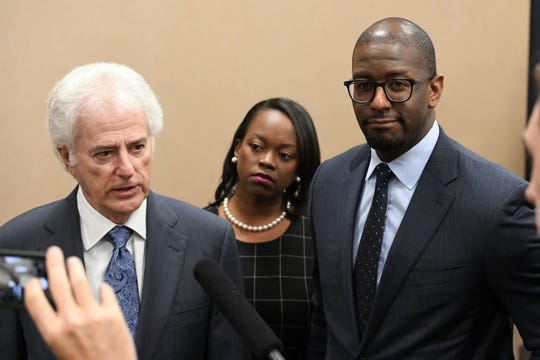 Former Mayor Andrew Gillum, right, and his wife, R. Jai Gillum, center, listen as Gillum's attorney Barry Richard addresses the media after it was announced that he settled with the Florida Commission on Ethics Wednesday, April 24, 2019.
