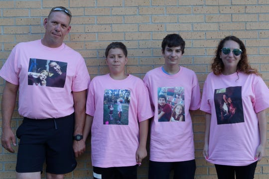 Joseph Weinman, father, left, Austin Weinman, brother, Kyle Weinman, brother, and Sara Weinman, mother of Mariah Weinman, the 8-year-old girl who was killed when a branch fell on their home during a storm last Friday, stand together for a photograph of the family wearing shirts with a photo of Mariah on them Tuesday, April 23, 2019.