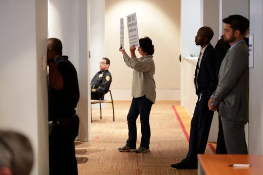 """Aine Ryan, a Tram Road resident, holds up a sign reading """"say no to transmission power lines"""" during a City Commission meeting at City Hall Wednesday, April 24, 2019."""