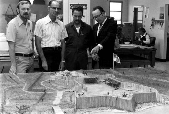 Key persons responsible for research and development of the model of Fort Gadsden now on display at the new museum are shown looking at the finished replica. Standing, left to right, are Patrick Elliot, museum artist; Eddie Nesmith of Apalachicola, retired park supt. At the historic site; Jesse Fairley Jr., museum preparatory; and William Greer of Eastpoint, military miniature figure designer.