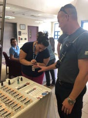 """St. Lucie County Fire Rescue Engineer Scott Miller gets his """"MANicure"""" from Nicole Hughes, of the Circuit 19 Guardian ad Litem Program."""