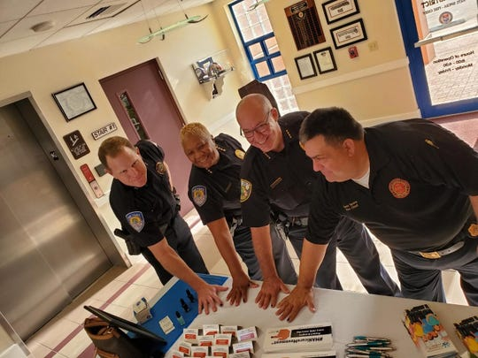 """Fort Pierce Police Deputy Chief Robert Ridle, left, Fort Pierce Police Chief Diane Hobley-Burney, Port St. Lucie Police Chief John Bolduc and St. Lucie County Fire Chief Nate Spera show off their """"prevention blue"""" fingernail polish in observation of National Child Abuse Awareness and Prevention Month."""