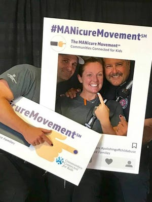 """St. Lucie County Fire Rescue Engineer Scott Miller, left, firefighter Michelle Thieson and Lt. Lewis Clanton show off their """"prevention blue"""" fingernail polish in observation of National Child Abuse Awareness and Prevention Month."""