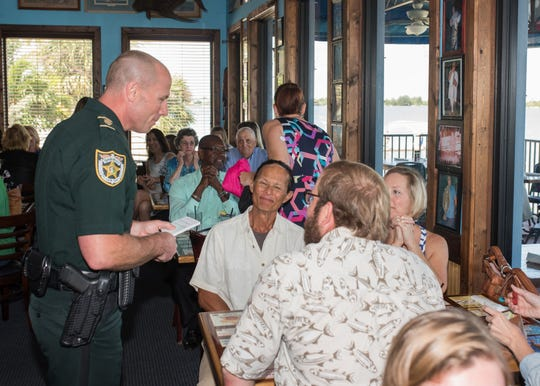St. Lucie County Sheriff's Office Major Brian Hester, left, serves customers with a smile during the 2019 fundraiser benefiting Donate Life Florida at Chuck's Seafood in Fort Pierce.