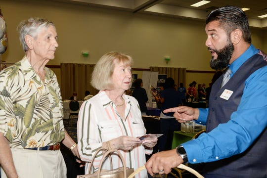 Raymond and Eleanor Foisy, left, speak with Erick Anderson of Lab Stop at the Treasure Coast Healthcare Summit April 13at the Port St. Lucie Civic Center.