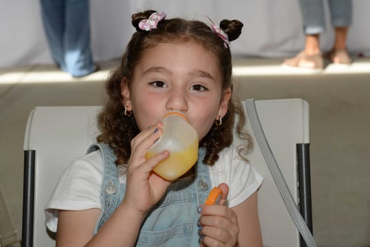 Sophia Varela enjoys a bottle of Natalie's Orchid Island juice at the Spring Forward for Hunger event in Indiantown, benefiting Treasure Coast Food Bank.