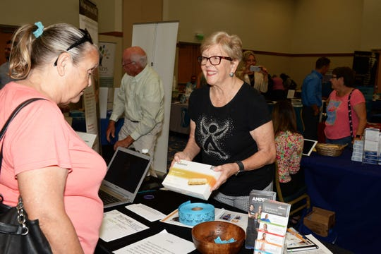 Debbie Becker, left, learns about Isagenix from Anne Mygatt at the Treasure Coast Healthcare Summit April 13at the Port St. Lucie Civic Center.