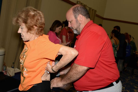 Dr. Wayne Palmer of Papa Chiropractic & Physical Therapy examines the spine of Marilyn Doane at the Treasure Coast Healthcare Summit April 13at the Port St. Lucie Civic Center.