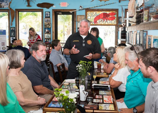 St. Lucie County Commissioner Chris Dzadovsky takes orders during the fourth annual Local Celebrity Lunch on April 7 at Chuck's Seafood in Fort Pierce. Pictured in the background are School Board member Kathryn Hensley, right, and County Commissioner Cathy Townsend, left.