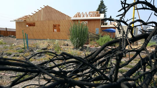 This Aug. 9 photo shows a burned tree in the foreground of Cheri Sharp's new home under construction in Santa Rosa. A measure in the California Legislature would toughen local governments' requirements for approving housing developments in high-risk areas.