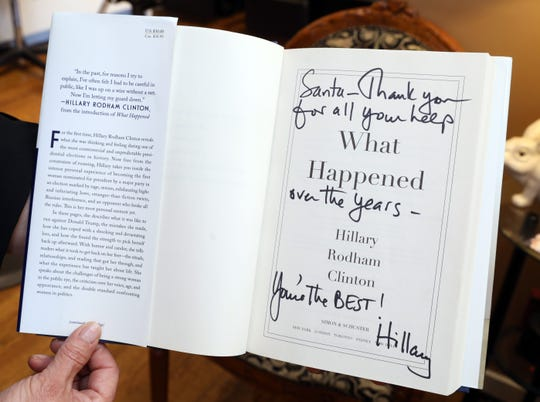 Santa Nikkels shows her personalized copy of Hillary Clinton's book at Santa's Hair Salon in Chappaqua April 23, 2019. Nikkels, an Ecuadorian immigrant who started the salon in Chappaqua twenty years ago, became the hairdresser of choice for Bill and Hillary Clinton.