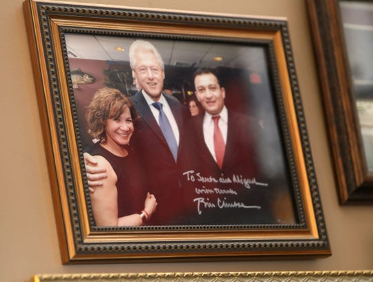 A signed photo of President Bill Clinton with Santa Nikkels and her husband Miguel Gonzalez hangs at Santa's Hair Salon in Chappaqua April 23, 2019. Nikkels, an Ecuadorian immigrant who started the salon in Chappaqua twenty years ago, became the hairdresser of choice for Bill and Hillary Clinton.