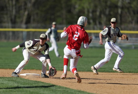 Clarkstown South's Trevor Montana (5) pulls in a throw as North Rockland's Nathaniel Guillen (2) attempts a steal during baseball action at Clarkstown South High School in West Nyack on Wednesday, April 24, 2019.