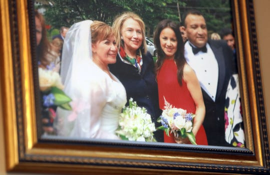A photo of Santa Nikkels with Hillary Clinton, her daughter and her husband on her wedding day hangs at Santa's Hair Salon in Chappaqua April 23, 2019. Nikkels, an Ecuadorian immigrant who started the salon in Chappaqua twenty years ago, became the hairdresser of choice for Bill and Hillary Clinton.