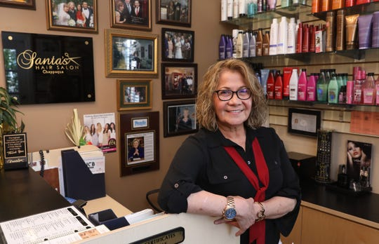 Owner Santa Nikkels beside a gallery of photos with the Clintons at Santa's Hair Salon in Chappaqua April 23, 2019. Nikkels, an Ecuadorian immigrant who started the salon in Chappaqua twenty years ago, became the hairdresser of choice for Bill and Hillary Clinton.