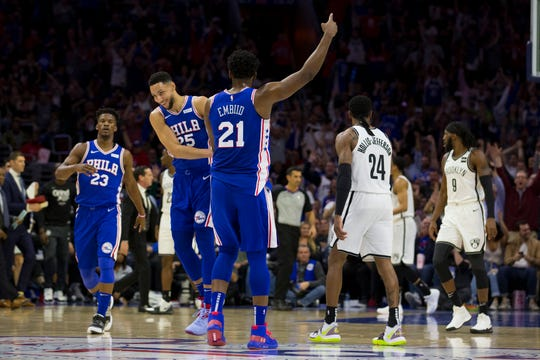 Joel Embiid #21, Ben Simmons #25, and Jimmy Butler #23 of the Philadelphia 76ers react in front of Rondae Hollis-Jefferson #24 of the Brooklyn Nets after a three-point basket by Embiid in the second quarter of Game Five of Round One of the 2019 NBA Playoffs at the Wells Fargo Center Tuesday.