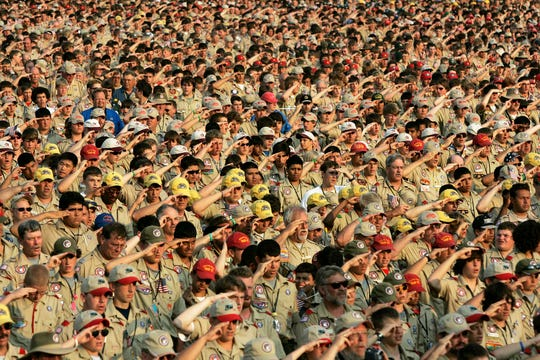 In this July 31, 2005 file photo, Boy Scouts salute as they recite the Pledge of Allegiance during the Boy Scout Jamboree in Bowling Green, Va. In 2019, financial threats to the Boy Scouts have intensified as multiple states consider adjusting their statute-of-limitations laws so that victims of long-ago child sex-abuse have a chance to seek redress in the courts.