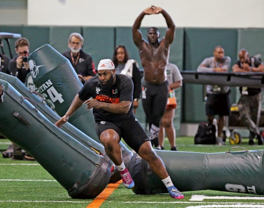 Miami defensive tackle Gerald Willis, front, runs through the tackling dummies as defensive end Joe Jackson stretches at the NCAA college football team's NFL Pro Day in Miami, Monday, March, 25, 2019. (Charles Trainor Jr./Miami Herald via AP)