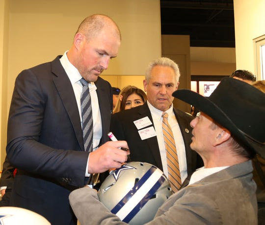 Dallas Cowboys All-Pro tight end Jason Witten autographs a helmet while touring the Texas Sports Hall of Fame before the 2019 induction ceremonies, Saturday, March 30, 2019, in Waco, Texas. (Rod Aydelotte/Waco Tribune Herald via AP)