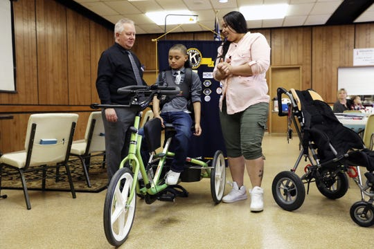 Amber Jones shows her son, Jahkryi Wicker, 10, his new trike donated by the Zanesville Kiwanis and Key Clubs from five high schools. Zanesville Kiwanis president Jeff Pickett is at left.