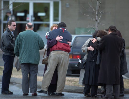 Connecticut State Lottery workers gather together outside of lottery headquarters in Newington, Conn., on March 10, 1998, their first day back at work after a shooting.
