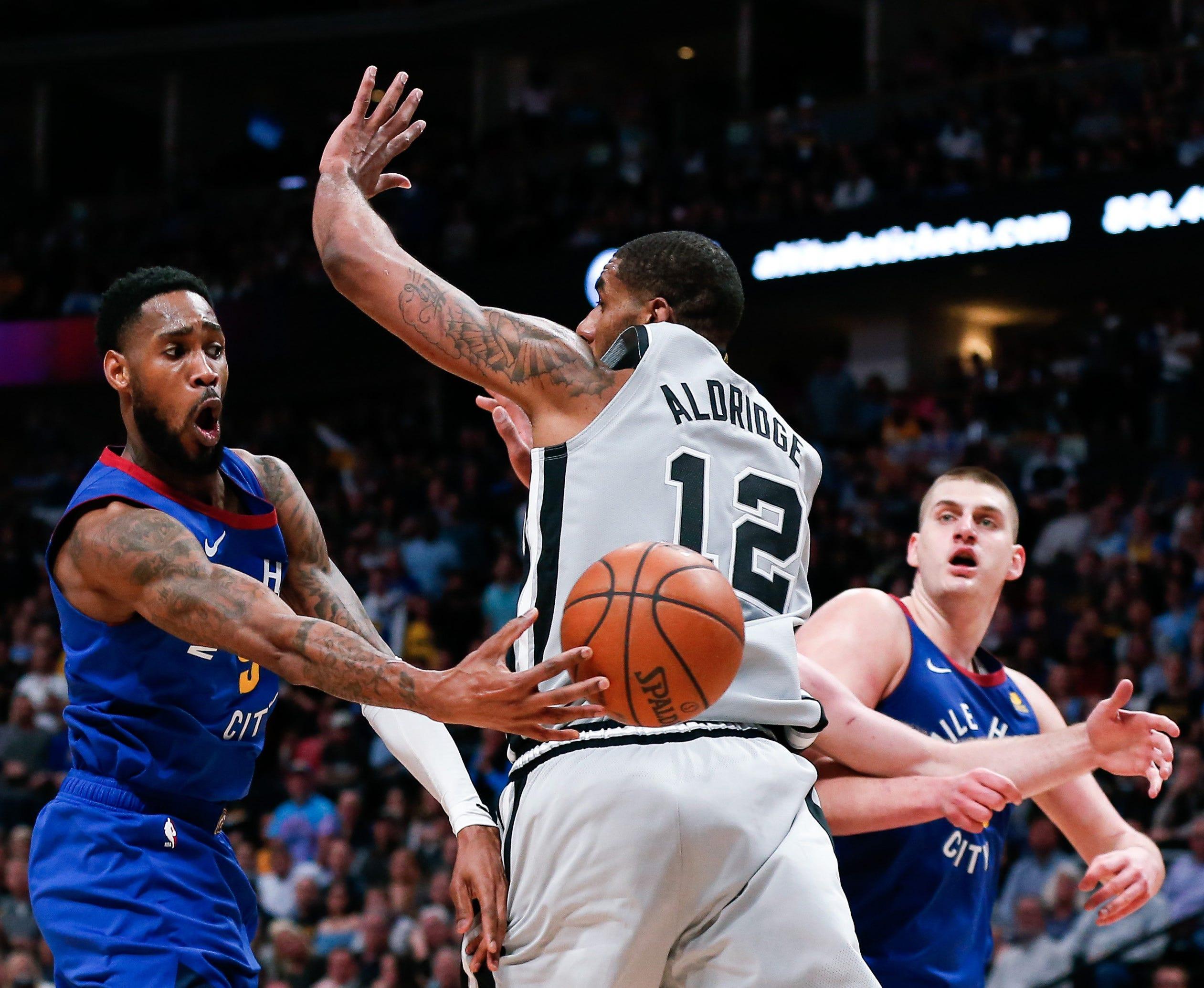 April 23: Denver Nuggets guard Will Barton (5) passes the ball to center Nikola Jokic (15) around San Antonio Spurs center LaMarcus Aldridge during Game 5 at the Pepsi Center.