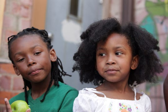 Menelik Swyer, 9, of Detroit, (left) and his sister Naja Swyer, 6, of Detroit enjoy green apples during the National Natural Hair meetup at the Artist Village in Detroit on Saturday, May 19, 2012.  The California State Senate on April 22, 2019 passed a bill that would ban schools and workplaces from having dress codes against braids, twists and other natural hair styles.