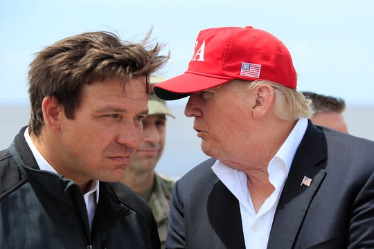 President Donald Trump talks to Florida Gov. Ron DeSantis, left, during a visit to Lake Okeechobee and Herbert Hoover Dike at Canal Point, Fla., on March 29, 2019.