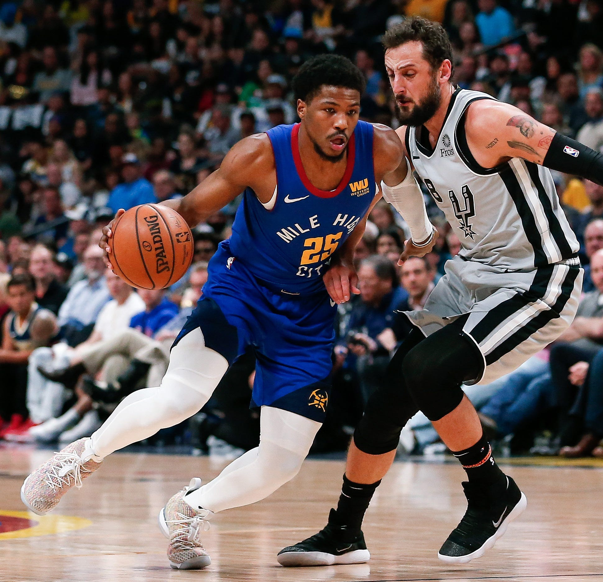 The Denver Nuggets' Malik Beasley controls the ball against San Antonio Spurs guard Marco Belinelli.
