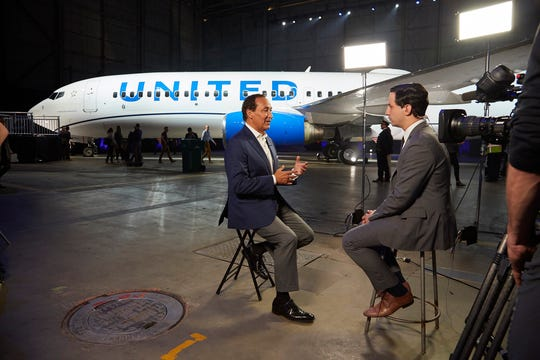 United Airlines CEO Oscar Munoz sits for a TV interview after the unveiling of the new livery.