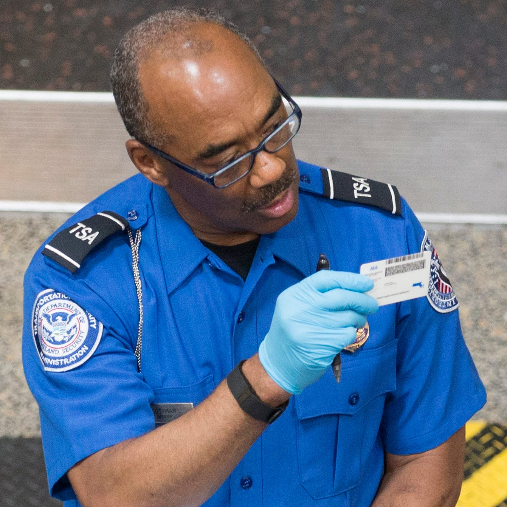 A TSA employee inspects travelers' identification at Reagan National Airport on June 30, 2016.