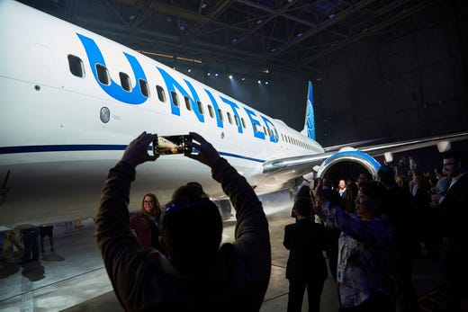 Employees take photos as United Airlines unveiled its new livery on a 737-800 at Chicago O'Hare airport