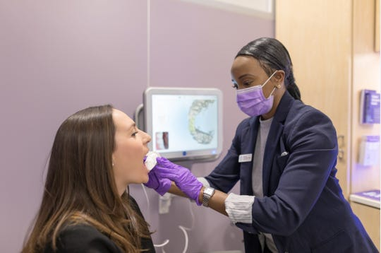 A SmileDirectClub customer gets her mouth scanned at a CVS store for removable clear plastic aligners.