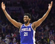 Joel Embiid reacts after making a three-point shot against the Brooklyn Nets.