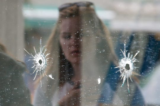 A woman looks at the bullet holes on the window of IV Deli Mark where a shooting took place on May 24, 2014, in Isla Vista, Calif.